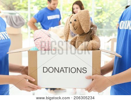 Two volunteers holding box with donated toys indoors