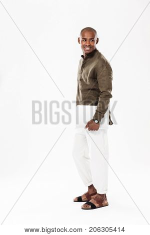 Full length side view image of smiling african man holding laptop computer and looking back over white background