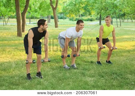 Young sporty men with dumb-bells doing exercise outdoors