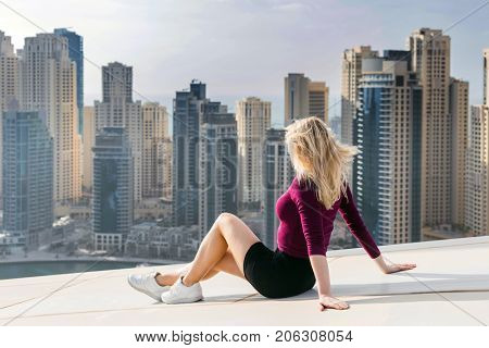 Young woman sits on rooftop of skyscraper in Dubai Marina area in Dubai, UAE