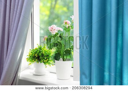 Beautiful view of houseplants on windowsill and curtains