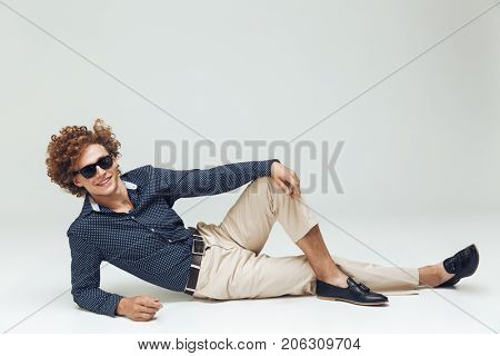 Photo of handsome young retro man dressed in shirt lies on floor and posing isolated. Looking camera.