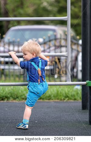 Portrait of toddler child outdoors wearing shorts and suspenders. One year old baby boy at playground