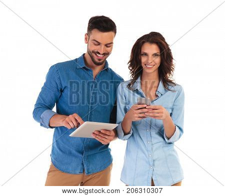 casual young couple working on different mobile devices on whit background