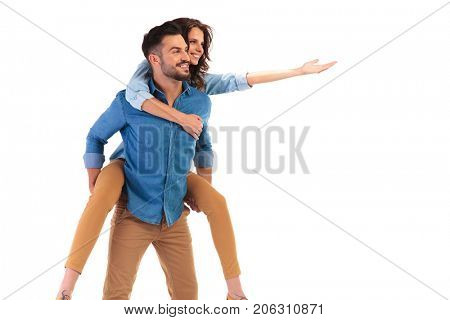 side view of a laughing casual couple presenting something and looking away from the camera on white background