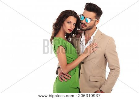 elegant man in sunglasses and suit embracing his woman; young modern couple standing embraced on white background