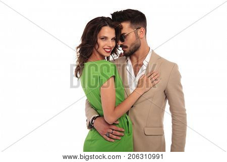 young elegant embraced couple on white background; young woman laughing while embracing her man