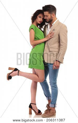 sexy young couple standing together, woman leaning on her man while holding one leg up on white background