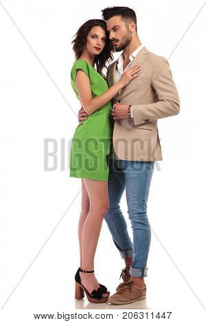 smiling woman in green dress embraces her elegant man on white background; elegant couple standing , full body picture