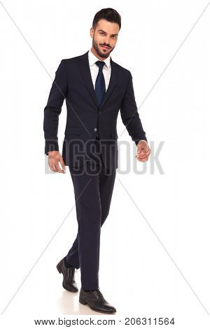 side view of a modern smiling business man walking and looking at the camera on white background
