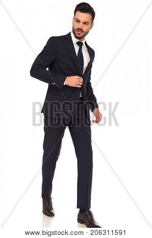 side view of a walking young business man looking away from the camera on white background