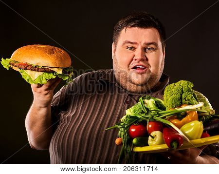 Diet fat man who makes choice between healthy and unhealthy food . Overweight male with hamburgers and vegetables trays trying to lose weight first time on black background. Treatment of constipation.