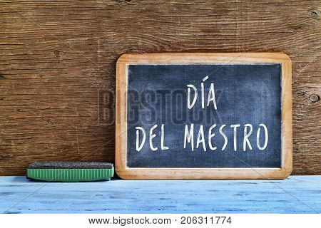 a chalkboard with the text dia del maestro, teachers day written in Spanish, and an eraser on a rustic wooden table, with a retro effect