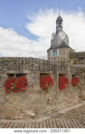 Flowers in the wall in front of clock tower at the walled city of Concarneau, Finistere, France