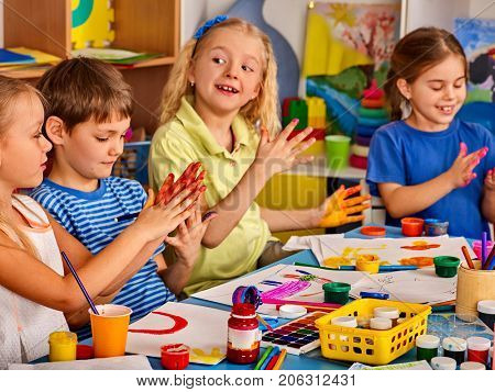 Small students with teacher finger painting in art school class. Break school in painting class. Mom and kids at home. Craft drawing education develops creative abilities of children. Children indulge