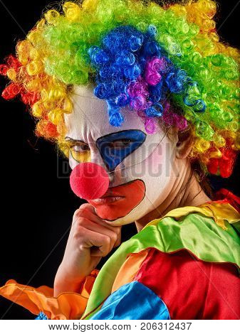 Evil clown on black background. Portrait of mad woman with angry look. Person hates working with children.