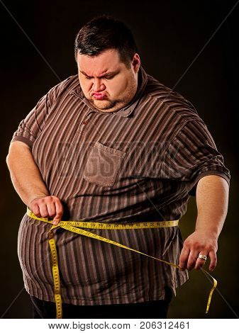 Man belly fat with tape measure weight loss around body on black background. First day of diet. Person is obese. Treatment of constipation.