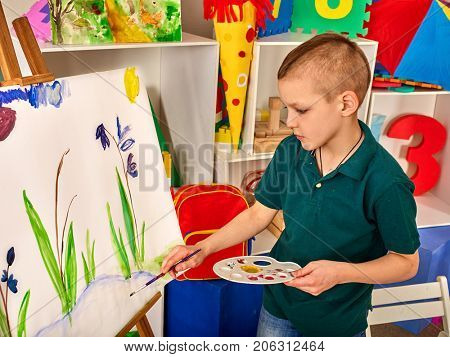 Child painting on easel. Kid boy learn paint by brush in class school. Kindergarten interior on background. Boy is getting ready to become an artist. Preparing for a children's art exhibition.