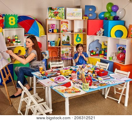 Children painting finger on easel. Group of kids girl and boy with teacher learn paint in class school. Child picture on background. Students draw a rainbow. Preparing for a children's art exhibition.