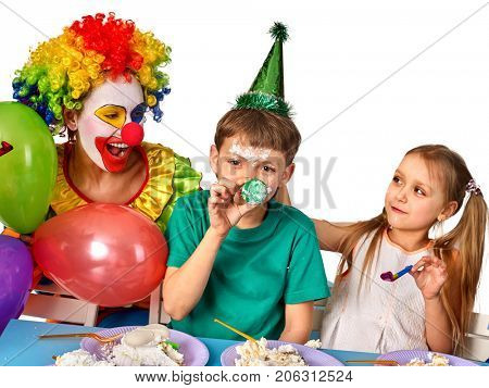Birthday children clown eating cake with two girl together. Kids with messy face have tier cake fight on isolated. Holiday on the occasion of the beginning of holidays.