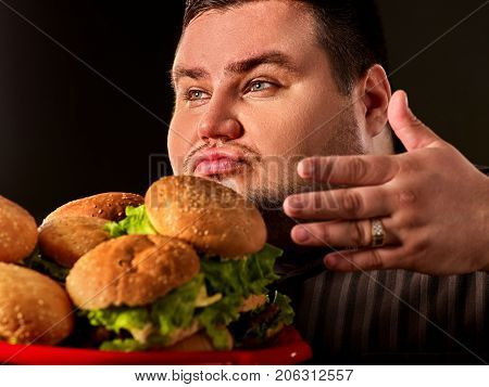 Fat man eating fast food hamberger and carries treat for friends on tray. Hamburgers close-up. Person regularly overeats concept on black background. Fatso with tray of harmful food.