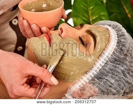 Collagen face mask. Facial skin treatment. Elderly woman 50-60 years old receiving cosmetic procedure in beauty salon. Healing clay against wrinkles. Therapeutic mud for home masks.