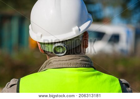 Rear view of construction worker on a building site and dressed in safety clothing of hard hat and high visibility vest