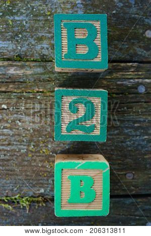 Children's wooden toy blocks spelling B2B on a weathered wooden background.