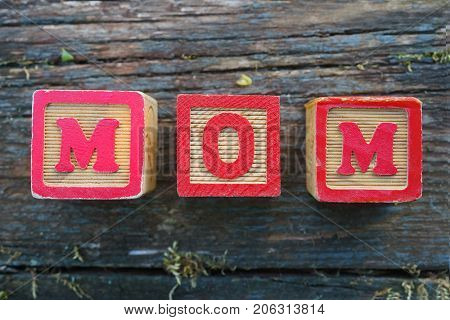 Children's wooden toy blocks spelling MOM on a weathered wooden background.