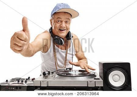 Elderly DJ playing music on a turntable and making a thumb up sign isolated on white background