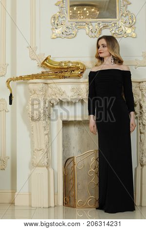 Woman in black dress stands near fireplace with big sax sits in baroque studio