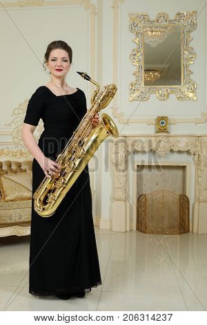 Woman in black dress hold baritone saxophone in baroque studio with mirror