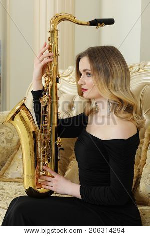 Pretty woman in black dress with big sax sits on couch in baroque studio