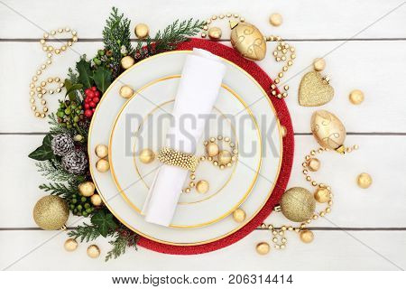 Christmas dinner table setting with porcelain plates, serviette, gold decorations and foil wrapped chocolates, with holly, mistletoe, ivy and fir on distressed white wood background