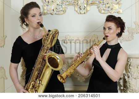 Two women in long dresses play saxophones in baroque studio with molding