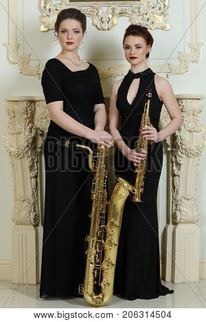 Two women in long dresses poses with saxophones in baroque studio