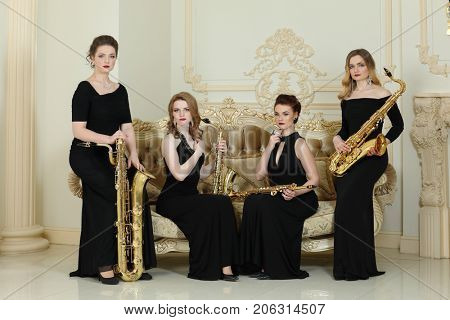 Four women in long dresses poses with saxophones near couch in studio