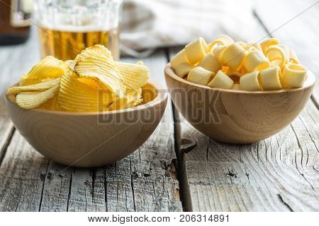 Crispy potato chips and rings in bowl. Salted potato chips.