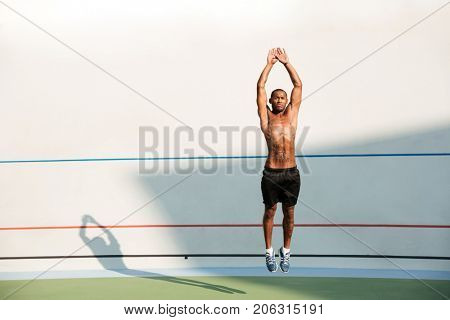 Full length portrait of a half naked african fitness man jumping at the track field outdoors