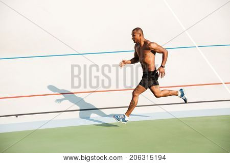 Full length portrait of a strong half naked sportsman running on a track field outdoors