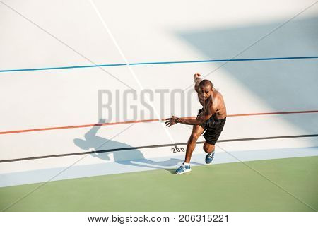 Full length portrait of a half naked healthy sportsman starting to run on a track field outdoors