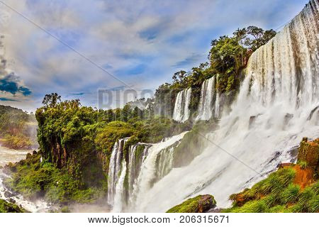 Waterfalls Iguazu on the border of Argentina, Brazil and Paraguay. Picturesque basaltic ledges form the famous waterfalls. The concept of active and exotic tourism