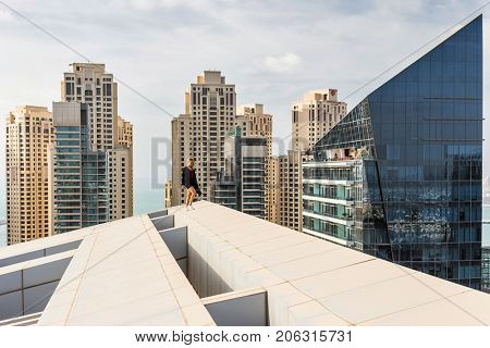 DUBAI, UAE - JAN 13, 2017: Woman on roof near Silverene Tower RMJM (on right), Designed by RMJM, this complex offers 35 floors in Tower A and 26 floors in Tower B