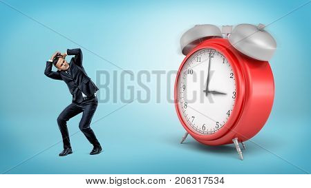 A scared businessman hides away from a giant red alarm clock standing on blue background. Working late. No leisure time. Start work early.