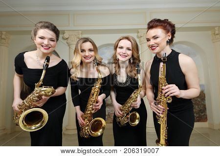 Four beautiful women in black dresses with saxophones smiles in studio with pilasters