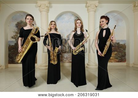 Four women in black dresses stand with saxophones in studio with pilasters