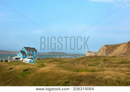 Beautiful blue house by the sea.  Rugged cost line of Havre Aubert in magdalen island in Quebec, Canada