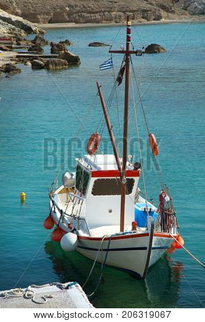 Fishing boat floating on turquoise water at Mandrakia in Milos Island in Cyclades in Greece