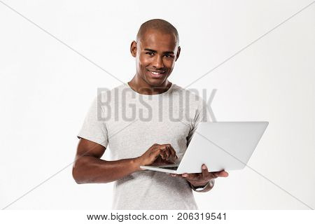 Image of happy young african man standing isolated over white background using laptop computer. Looking camera.