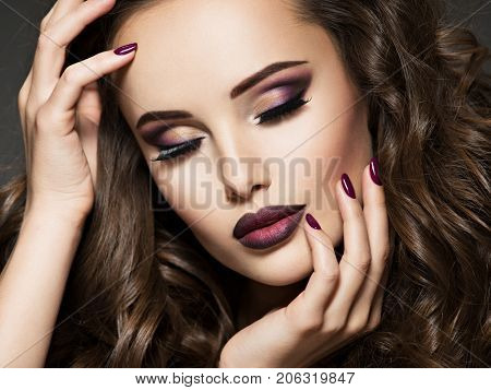 Beautiful face of  young woman with maroon makeup. Portrait of gorgeous girl with vinous lips